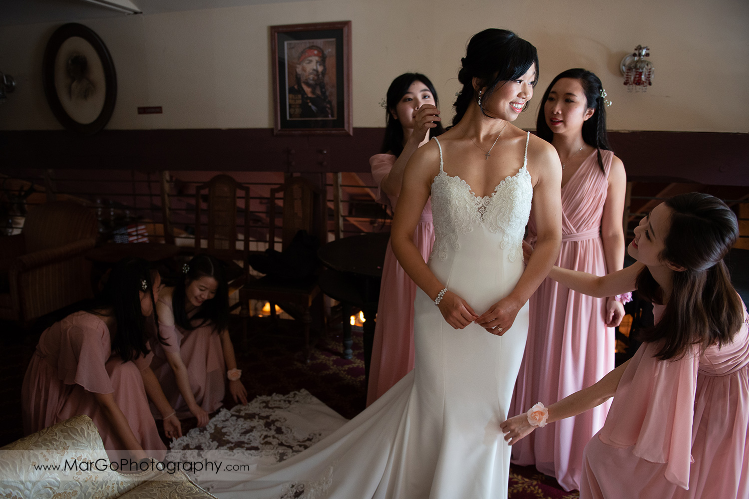 bridesmaids in pink dresses fixing bride's wedding dress at Long Branch Saloon & Farms in Half Moon Bay