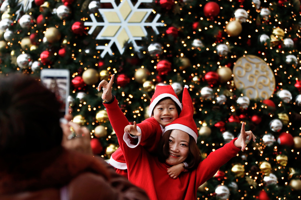 . A woman and her child wearing Santa Claus hats pose for a souvenir photo in front of a Christmas tree decorated at a shopping mall in Beijing, Sunday, Dec. 25, 2016. Although Christmas is not traditionally celebrated in China, shopping malls and retailers welcome the festival by organizing activities to attract shoppers as a chance to boost the year-end sales. (AP Photo/Andy Wong)