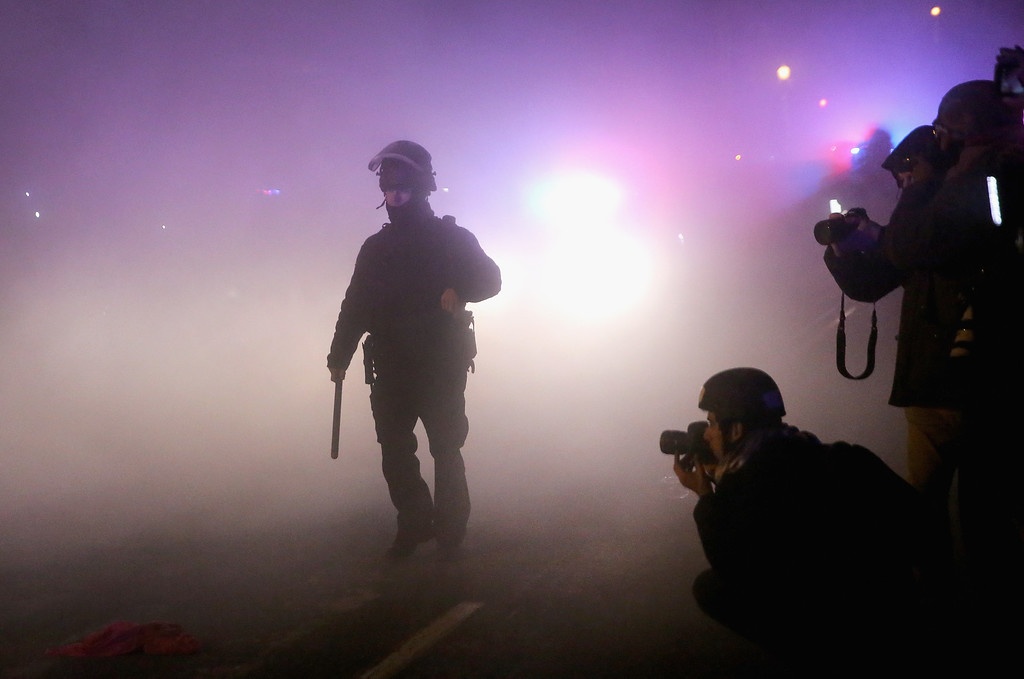 . Police stand guard in front of a smoldering squad car after it was set on fire by demonstrators during a protest on November 25, 2014 in Ferguson, Missouri. Yesterday protesting turned into rioting after the announcement of the grand jurys decision in the Michael Brown case. Brown, an 18-year-old black man, was killed by Darren Wilson, a white Ferguson police officer on August 9. At least 12 buildings were torched and more than 50 people were arrested during the night-long rioting.  (Photo by Scott Olson/Getty Images)