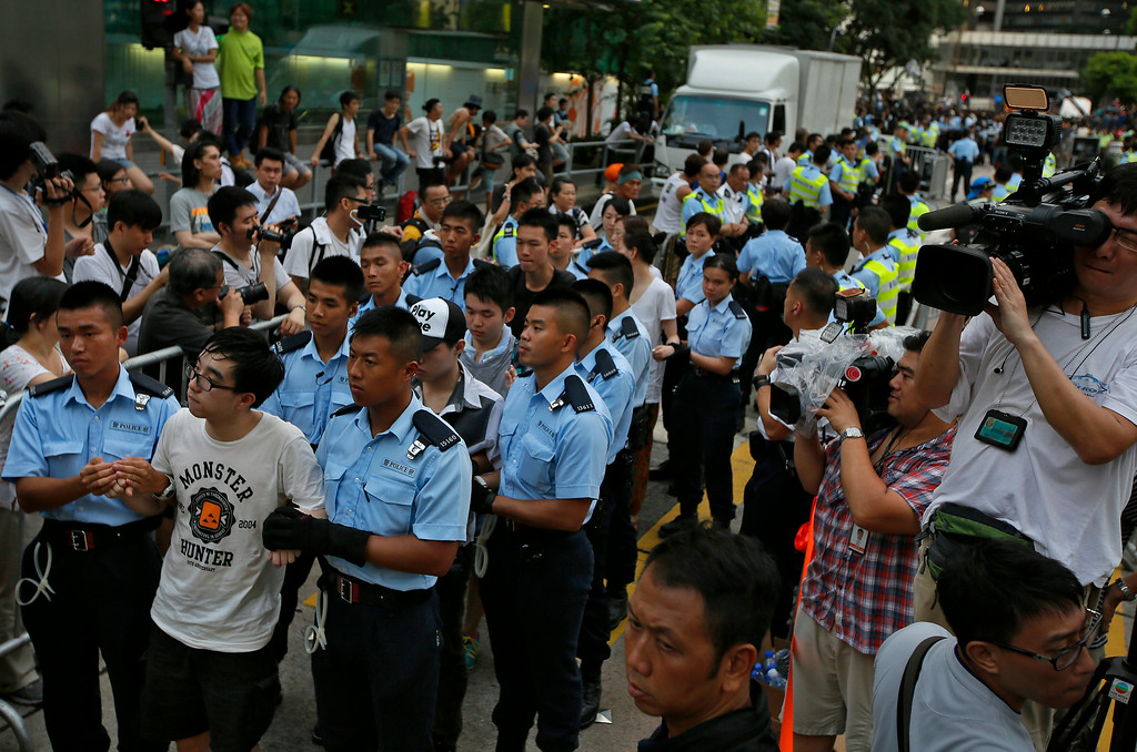 . Protesters are arrested by police officers after hundreds of protesters staged a peaceful sit-ins overnight on a street in the financial district in Hong Kong Wednesday, July 2, 2014, following a huge rally to show their support for democratic reform and oppose Beijing\'s desire to have the final say on candidates for the chief executive\'s job. (AP Photo/Vincent Yu)