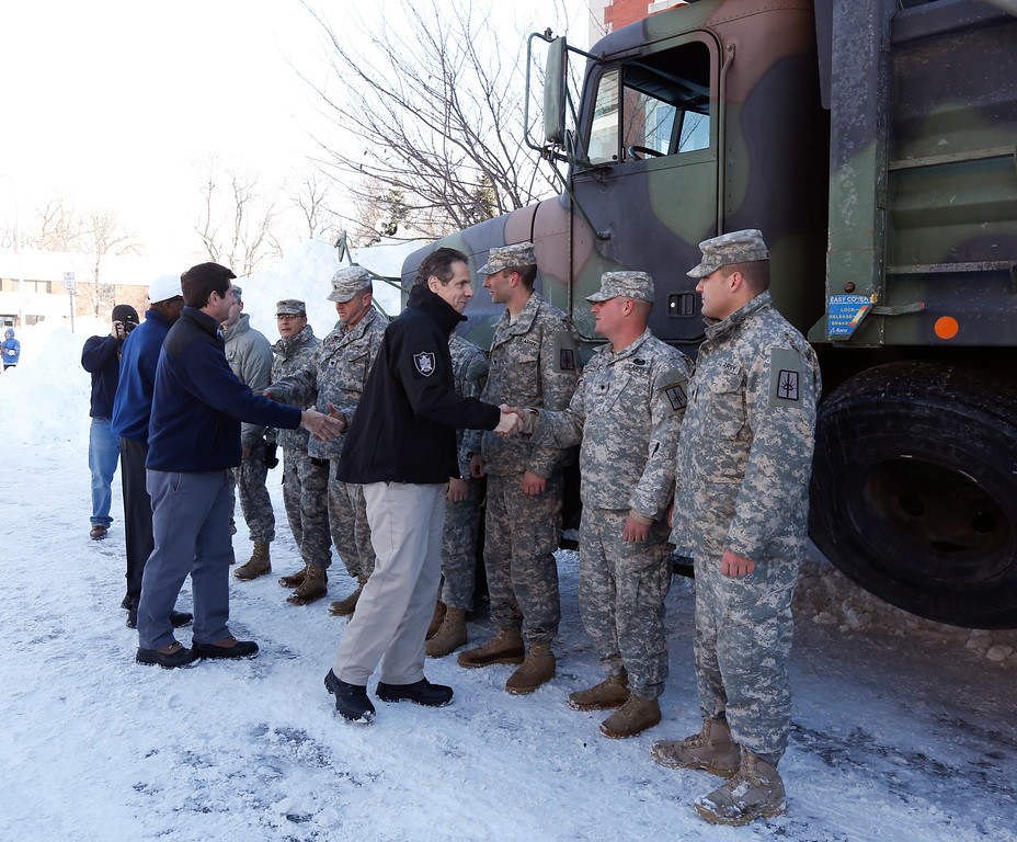 . New York Gov. Andrew Cuomo thanks National Guard members in south Buffalo for their help clearing streets after heavy lake-effect snowstorms in western New York on Friday, Nov. 21, 2014, in Buffalo, N.Y. A snowfall that brought huge drifts and closed roads in the Buffalo area finally ended Friday, yet residents still couldn\'t breathe easy, as the looming threat of rain and higher temperatures through the weekend and beyond raised the possibility of floods and more roofs collapsing under the heavy loads. (AP Photo/Mike Groll)