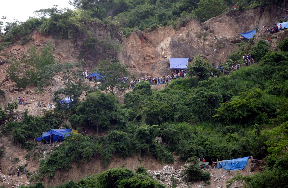 . People gather outside a gold mine where a landslide trapped miners working inside, in San Juan Arriba, Choluteca in southern Honduras, Thursday, July 3, 2014. The entrance to the artisanal mine has a vertical entrance, is located on a steep slope, and operated by local residents. (AP Photo/Fernando Antonio)