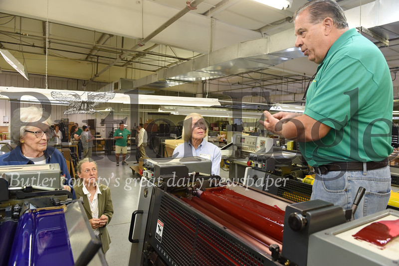 Harold Aughton/Butler Eagle: (left - right) Shirley Winkler, Eagle Printing owner, Karen Wise; and Joanne Fudoli listen to pressman Jack Puchak as he explains the printing process of the company's six-color press during the company's 100th anniversary celebration Wed., Sept. 18.