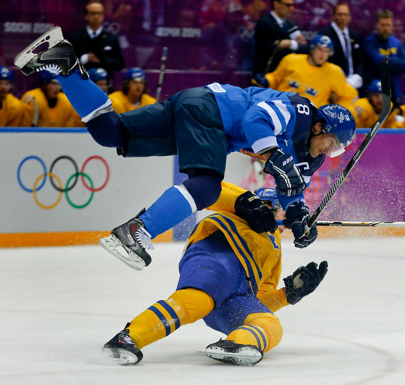 . Finland forward Teemu Selanne trips over a Swedish player during the second period of a men\'s semifinal ice hockey game at the 2014 Winter Olympics, Friday, Feb. 21, 2014, in Sochi, Russia. (AP Photo/Julio Cortez)