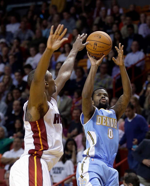 . Denver Nuggets guard Aaron Brooks (0) shoots against Miami Heat forward Chris Bosh (1) during the second half of an NBA basketball game in Miami, Friday, March 14, 2014. The Nuggets won 111-107. (AP Photo/Alan Diaz)