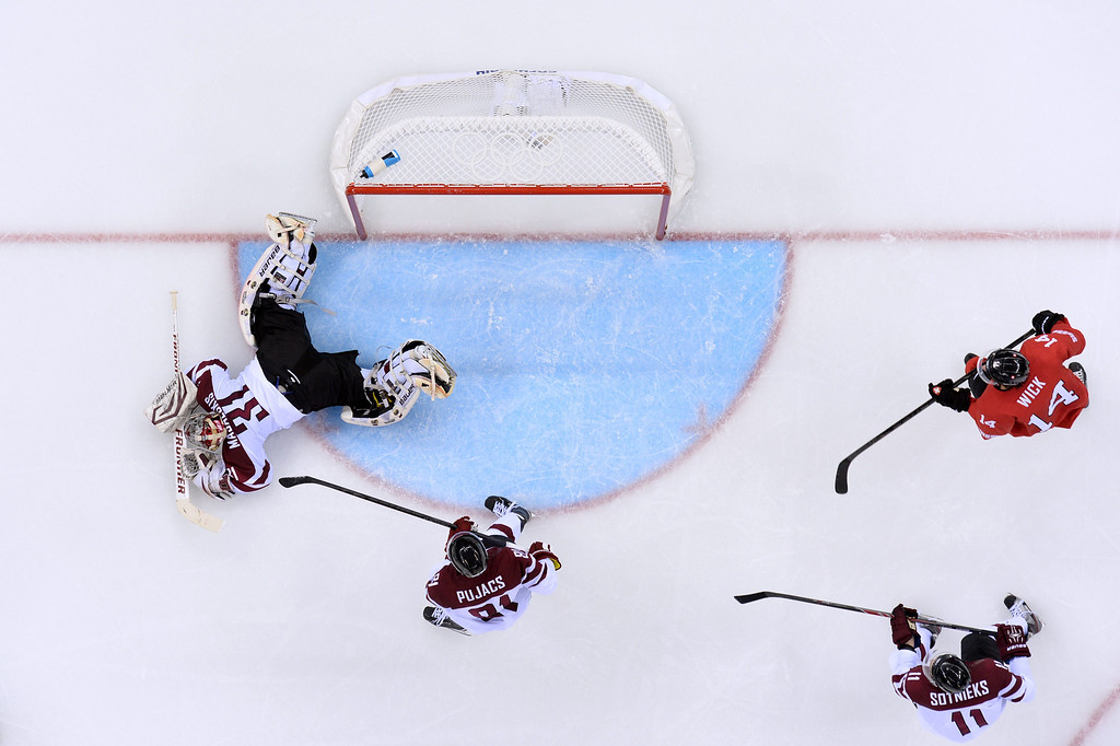 . (LtoR) Latvia\'s goalkeeper Edgars Masalskis, Latvia\'s Georgijs Pujacs and Latvia\'s Kristaps Sotnieks vie with Switzerland\'s Roman Wick in the Men\'s Ice Hockey Group C match Latvia vs Switzerland at the Shayba Arena during the Sochi Winter Olympics on February 12, 2014 in Sochi.  ANDREJ ISAKOVIC/AFP/Getty Images