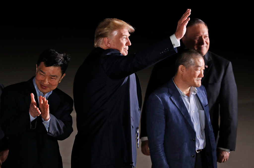 . President Donald Trump, accompanied by Secretary of State Mike Pompeo, back, waves at the media and others upon arrival of former North Korean detainees Tony Kim, left, Kim Dong Chul and Kim Hak Song, unseen, Thursday, May 10, 2018, at Andrews Air Force Base, Md. (AP Photo/Alex Brandon)