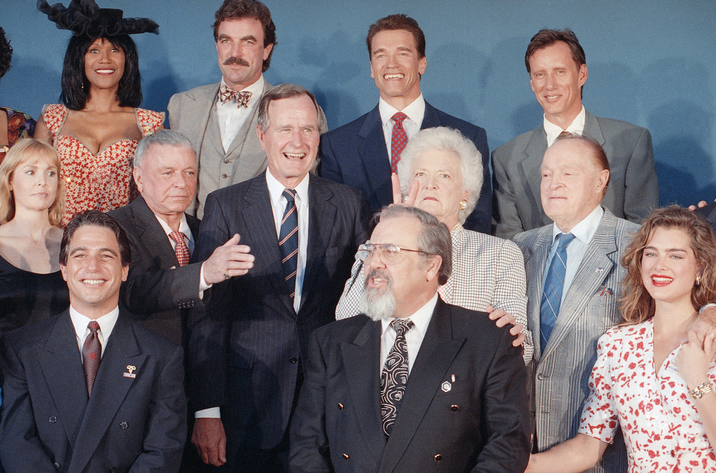 . Mrs. Barbara Bush, middle row, second from right, places two of her fingers behind the head of producer George Schlatter during a photo session at Universal City prior to the USOs 50th Anniversary party, Friday, April 5, 1991, Los Angeles, Calif. Front row, from left to right: actor Tony Danza, Schlatter, and actress Brooke Shields.  Second row, from left to right: unidentified woman, singer Frank Sinatra, Pres. George H. W. Bush and entertainer Bob Hope. Back row from left to right: unidentified woman, actors Tom Selleck, Arnold Schwarzenegger and James Woods. (AP Photo/Barry Thumma)