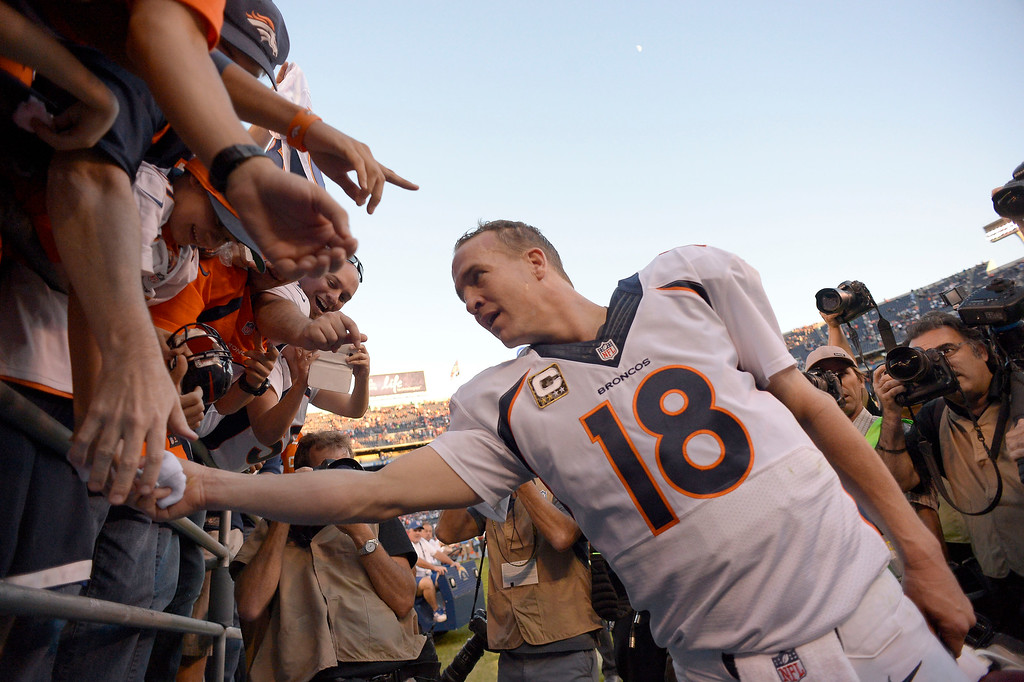 . Denver Broncos quarterback Peyton Manning (18) hands a young fan his wrist bands after their win over the San Diego Chargers at Qualcomm Stadium. (Photo by John Leyba/The Denver Post)