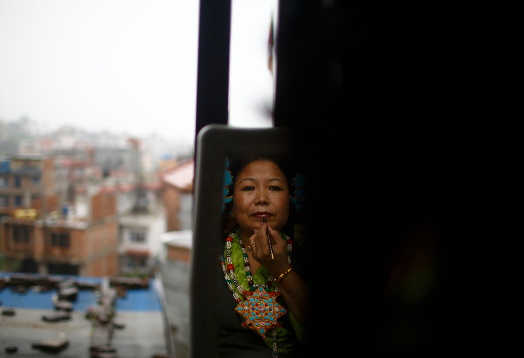. A Tibetan woman in traditional costume is reflected on a mirror as she applies makeup during celebrations of the 78th birthday of exiled spiritual leader Dalai Lama in Kathmandu July 6, 2013. During last month\'s visit of Chinese State Councilor Yang Jiechi, Chairman of the Interim Election Council Khil Raj Regmi said Nepal is firmly committed to the One-China Policy and reaffirmed its stand that the territory of Nepal will not be allowed to be used for any activities against China. Nepal ceased issuing refugee papers to Tibetans in 1989 and recognizes Tibet to be a part of China. REUTERS/Navesh Chitrakar