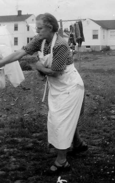 Charlotte Seifert in Connecticut taking clothes from the clothesline. 1954.