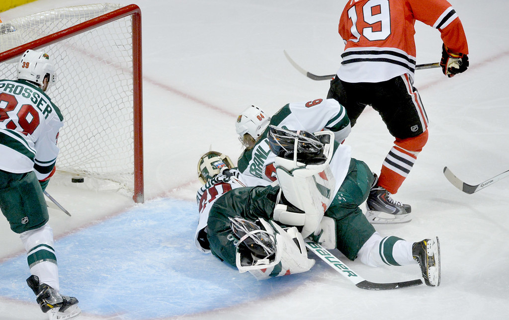 . Chicago\'s Jonathan Toews scores the Blackhawks\' winning goal on Minnesota\'s Ilya Bryzgalov, tangled up in the crease with teammate Mikael Granlund in the third period. (Pioneer Press: Ben Garvin)