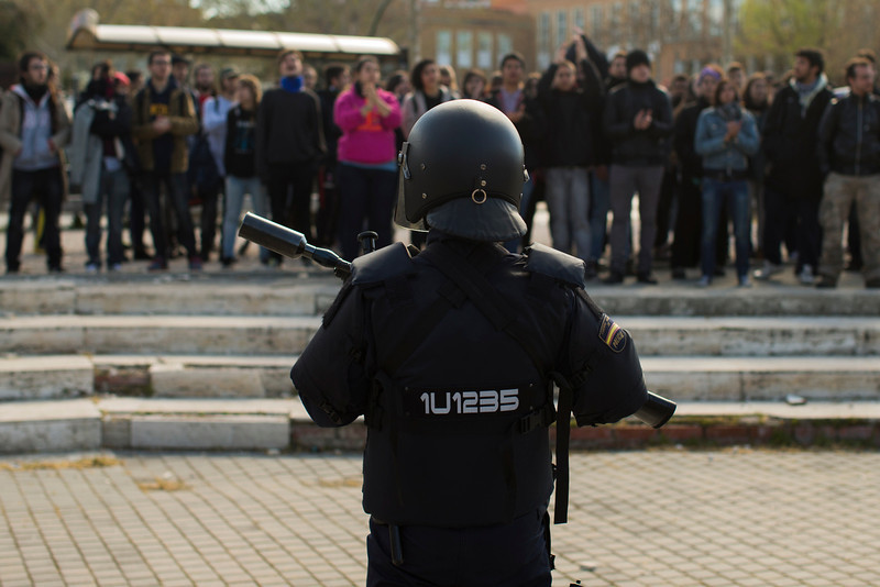 . A riot police officer stands guard as students shout slogans against the detention of other students during the first day of a student strike to protest a government education reform and cutbacks in grants and staffing, at Complutense Universtity in Madrid, Spain, Wednesday, March 26, 2014. Spanish police say they have arrested more than 50 students when the police moved in to end the occupation of a campus building after the university had asked them to intervene. Students, many with their faces covered, set fire to trash containers and set up barricades on at least two streets in the university complex during the protest. (AP Photo/Andres Kudacki)