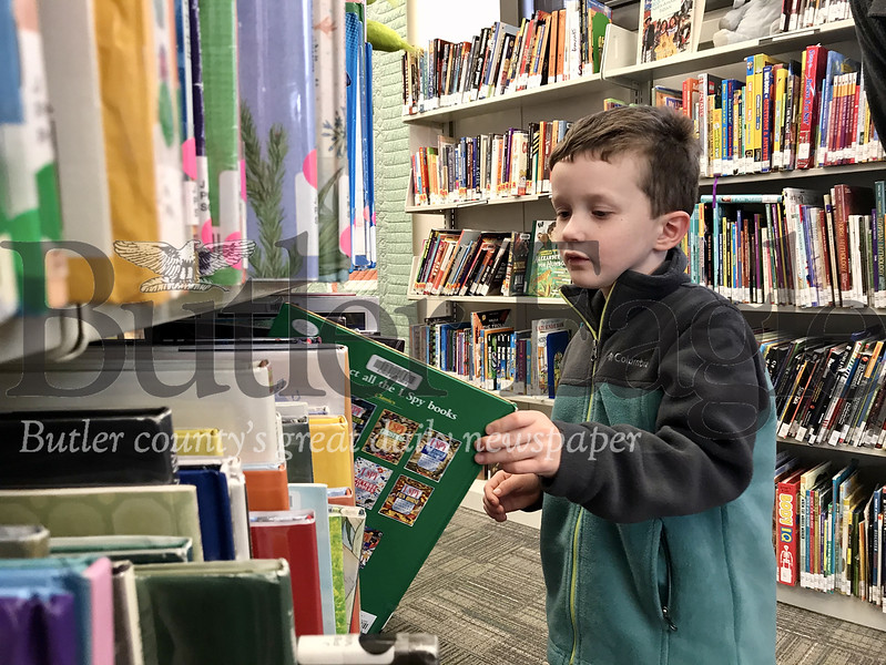 Will Pyda, 4, browses shelves at the Slippery Rock Community Library's children section Monday to find the next book he will read with his parents in the quest to reach 1,000 books before kindergarten. Photo by Gabriella Canales.
