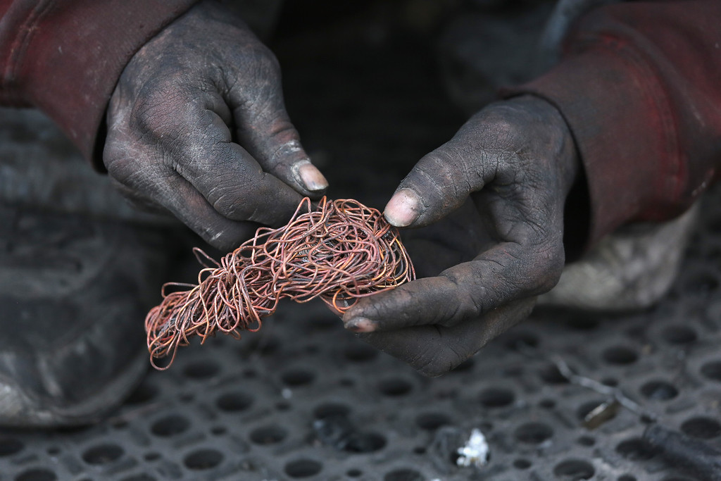 . NOGALES, MEXICO - MARCH 05:  Deported immigrant Jorge Dariel sorts copper he stripped from wiring that he found at the Tirabichi landfill on March 5, 2013 in Nogales, Mexico. He said he had been working in construction in Arizona for about 3 years when he was apprehended by U.S Customs and Border Protection agents and sent back to Mexico. About 30 families, including Jorge, live at the dump, searching for recyclables to sell for a living. He and others have received aid from the non-profit Home of Hope and Peace, which plans to expand it\'s assistance to the dump\'s impoverished populace in the future. (Photo by John Moore/Getty Images)