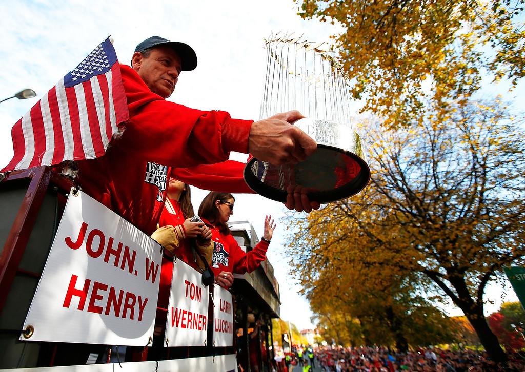 . BOSTON, MA - NOVEMBER 02:  President and Chief Exective Officer Larry Lucchino of the Boston Red Sox holds up the World Series trophy during the World Series victory parade on November 2, 2013 in Boston, Massachusetts.  (Photo by Jared Wickerham/Getty Images)