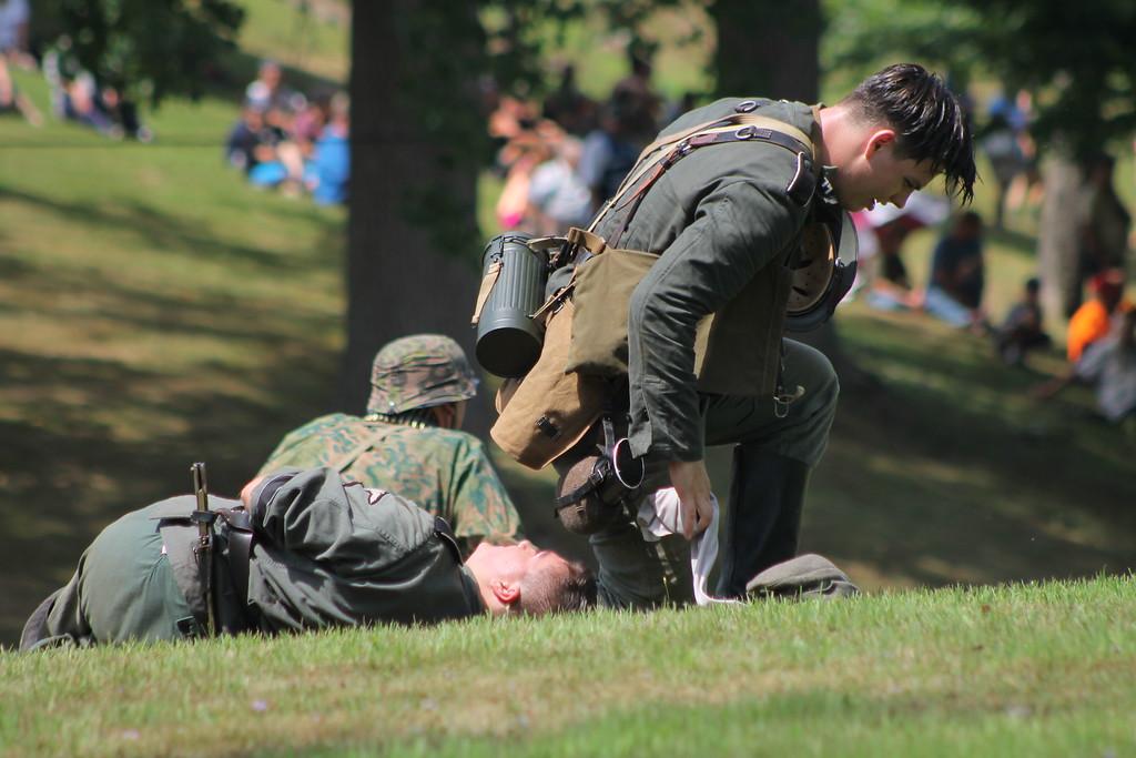 . Troops check fallen soldiers for fatalities during a gun battle reenactment at D-Day Conneaut 2018. Kristi Garabrandt - The News-Herald