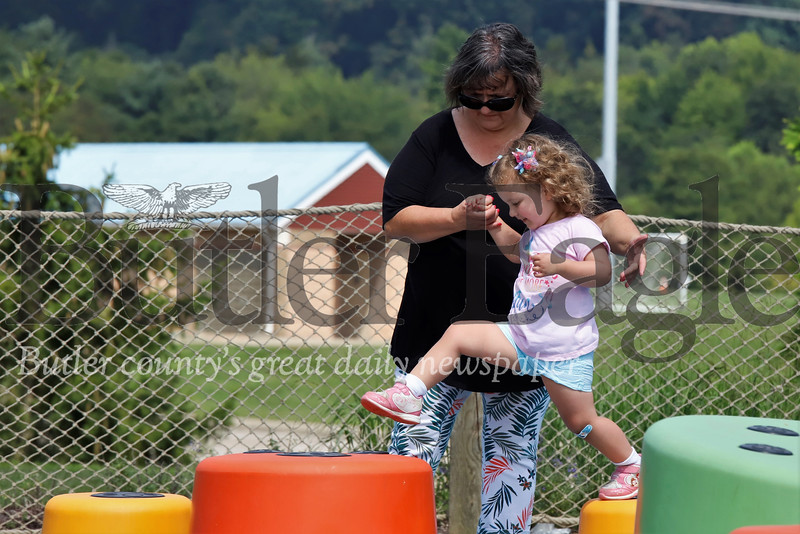 Jennie Langill, 2, of Cranberry hops from block to block at the Crocodile Cove Playground in North Boundary Park in Cranberry, with the help of her grandmother Marcella Nollinger Wednesday. Seb Foltz/Butler Eagle 07/31/19