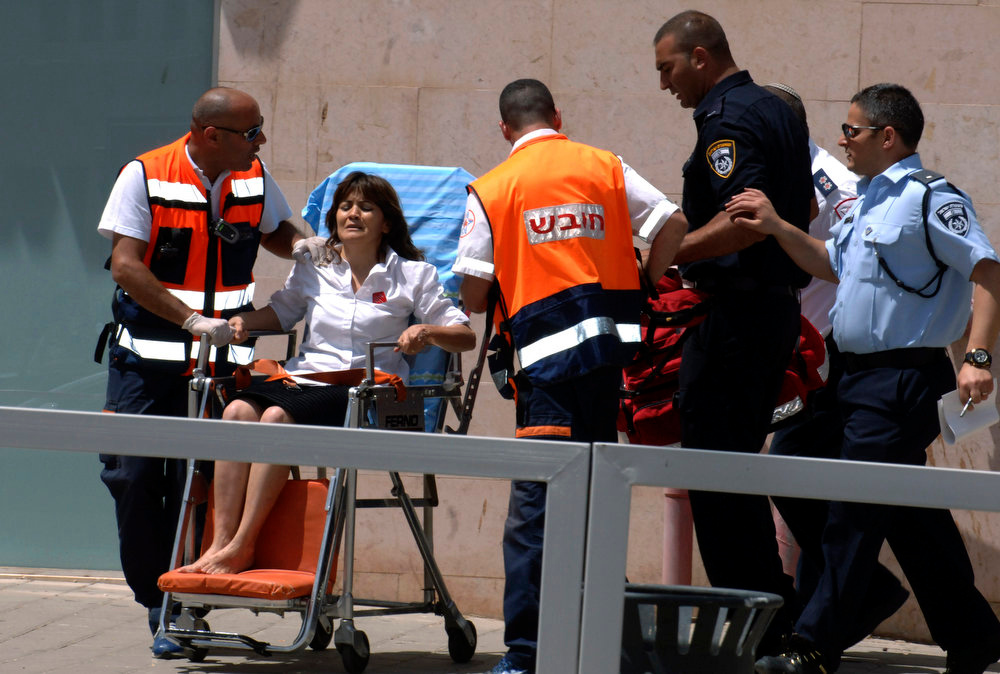 Description of . An Israeli woman is taken out of a bank in the town of Beersheba, Monday, May 20, 2013.  A gunman stormed into a bank in the southern Israeli city of Beersheba Monday, killing four people in a gunfight and taking a hostage before killing himself, police said. (AP Photo/Dudu Greenspan)