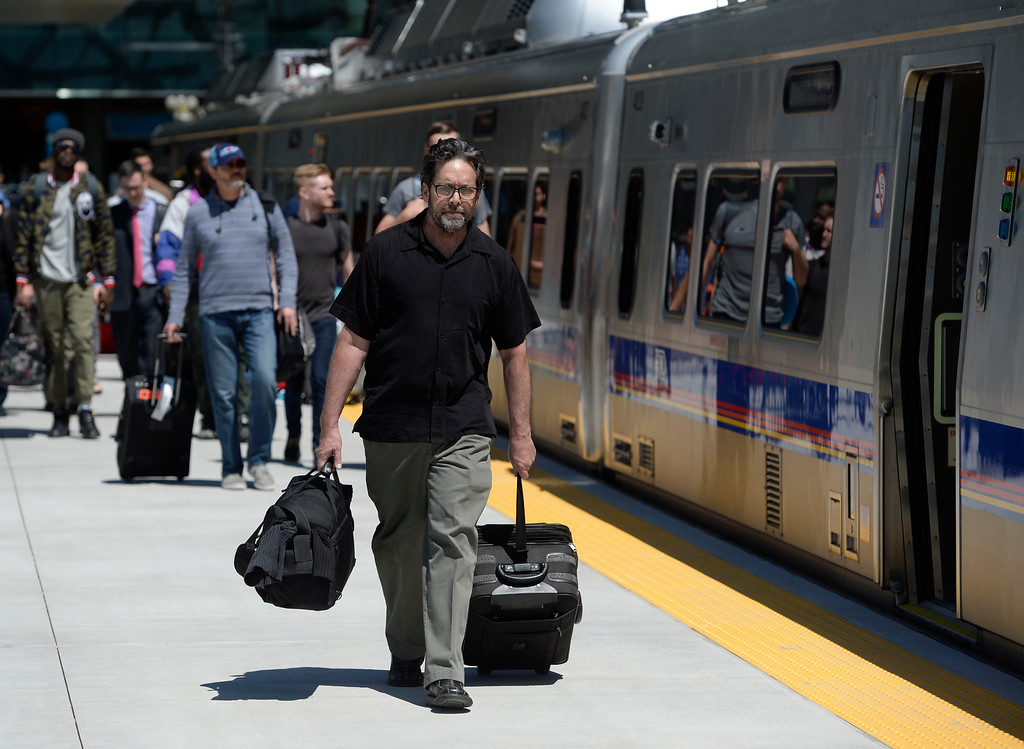 . Train passenger Greg Murphy heads to the the new RTD University of Colorado A-Line train to catch a ride into downtown Denver April 22, 2016. Murphy flew in from Orlando Florida. (Photo by Andy Cross/The Denver Post)