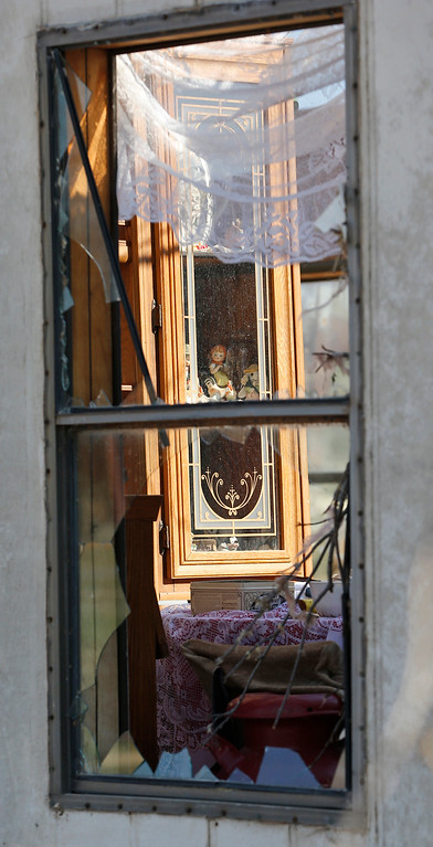. A china cabinet is seen through the window of a tornado-damaged home in the River Oaks Estate mobile home park in Sand Springs, Okla., Thursday, March 26, 2015. Gov. Mary Fallin has declared a state of emergency for 25 Oklahoma counties after powerful storms rumbled across the state Wednesday evening and produced tornadoes and flat-line winds that led to one death, numerous injuries and widespread damage. (AP Photo/Sue Ogrocki)