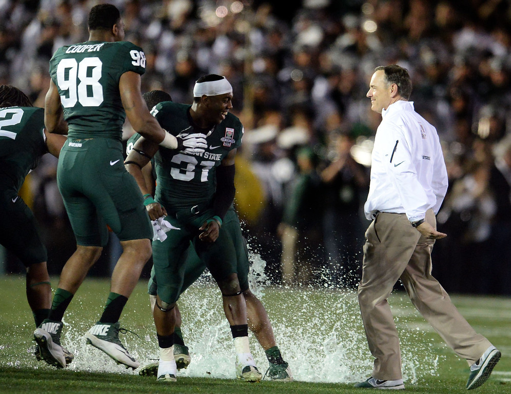 . Michigan State head coach Mark Dantonio, right, smiles after avoiding the gatorade bath after defeating Stanford 24-20 during the 100th Rose bowl game in Pasadena, Calif., on Wednesday, Jan.1, 2014. 