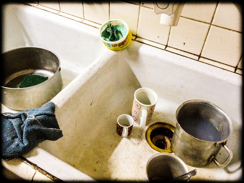 dishes in the sink and laundry detergent in the pot used as dish soap