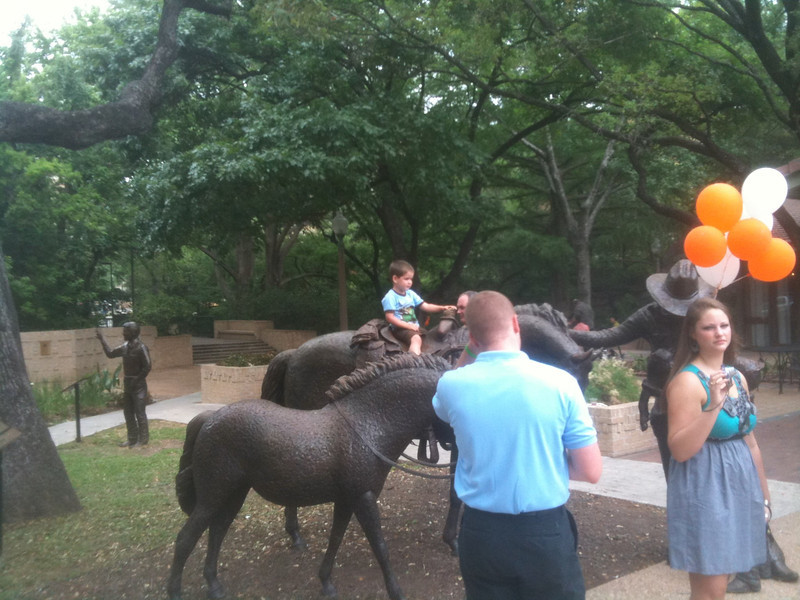 Riding the horse statues outside of the UT Aluumni center.  A future Longhorn grad, maybe?
