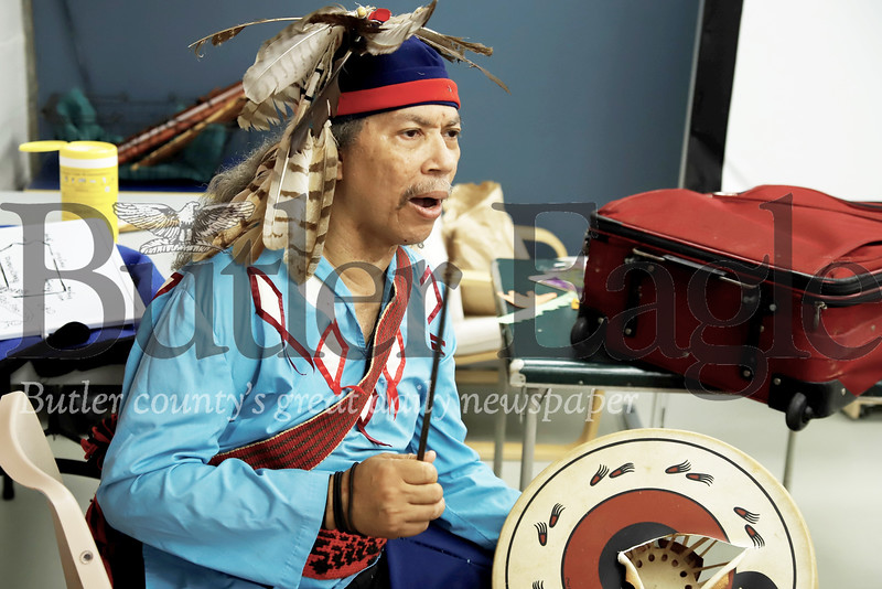 Miguel Sagne  of Pittsburgh sings a Native American song dressed in a traditional Seneca garb at a presentation at the Zeilienople Library earlier this month. Sagne himself is a Cuban born descendent of the South American Taino tribe. Seb Foltz/Butler Eagle