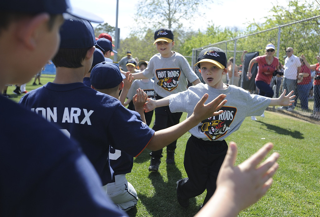 . LONG BEACH, CALIF. USA -- T-ballers get high-fives from older players as they enter opening ceremonies for The Los Altos Youth Baseball and Softball league at El Dorado Park in Long Beach, Calif. on March 2, 2013.  Photo by Jeff Gritchen / Los Angeles Newspaper Group