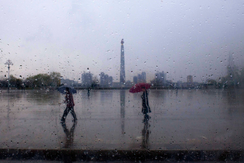 . North Koreans, seen through a raindrop spotted bus window, walk with umbrellas in front of the Tower of the Juche Idea in central Pyongyang, North Korea on Monday April 18, 2011.  (AP Photo/David Guttenfelder)