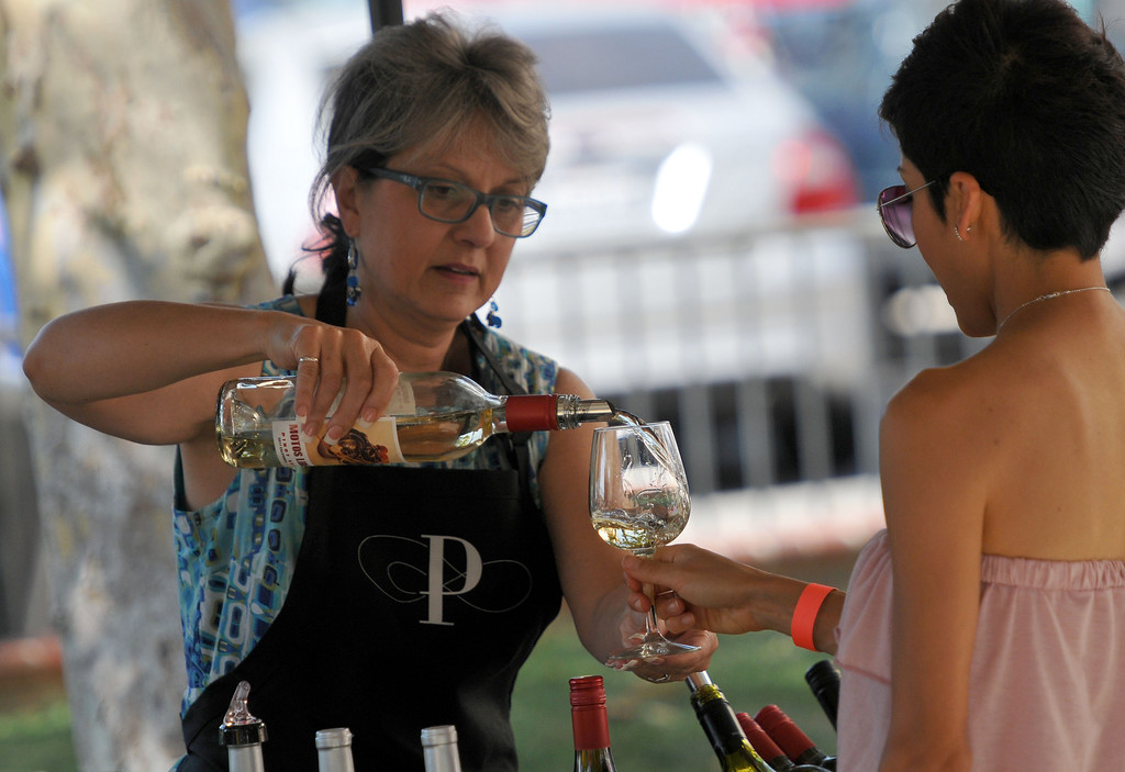 . (John Valenzuela/ Staff Photographer)  Maria Clark of Paxton Cellars Winery pours a glass of wine during the Redlands Wine, Beer, and Music event at Ed Hales Park in downtown Redlands, Saturday, June 22, 2013.