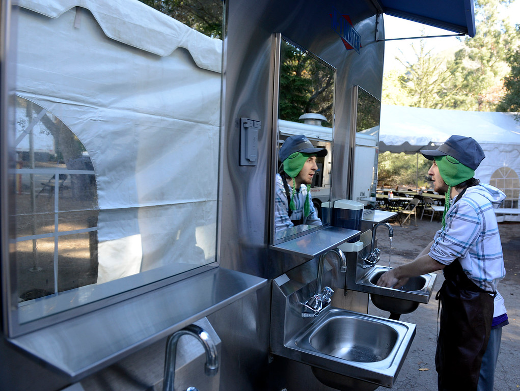 . Tyler Campuzano washes his hands in while working cleanup crew in the mobile dining area in the firefighters base camp for the Pfeiffer Ridge Fire in Pfeiffer Big Sur State Park on Friday December 20, 2013. (Photo David Royal/ Monterey County Herald)