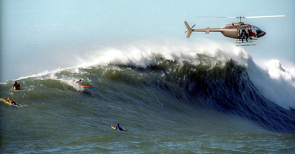 Description of . Film crew shoots Flea's takeoff from a helicopter that nearly gets swamped as the breaking wave splashes the rear rotor.  (Dan Coyro/Sentinel)