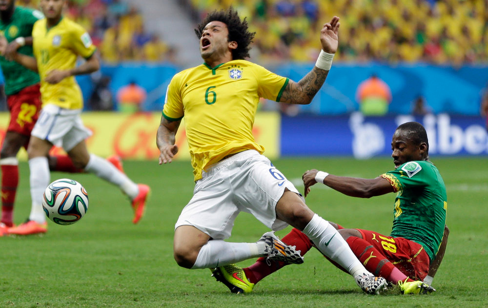 . Brazil\'s Marcelo is fouled by Cameroon\'s Eyong Enoh, right, during the group A World Cup soccer match between Cameroon and Brazil at the Estadio Nacional in Brasilia, Brazil, Monday, June 23, 2014. (AP Photo/Andre Penner)