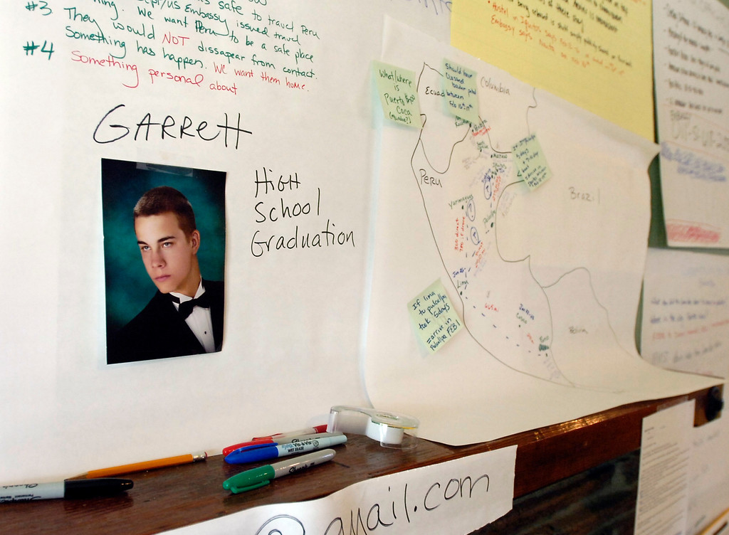 . Photos, maps, contacts and other information related to missing bicyclist Garrett Hand cover a wall at the home of Hand\'s mother Francine Fitzgerald in Concord, Calif. on Monday, Feb. 25, 2013. Hand and girlfriend Jamie Neal have not been heard from in a month after going missing during a bicycling trip in Peru. (Kristopher Skinner/Staff)