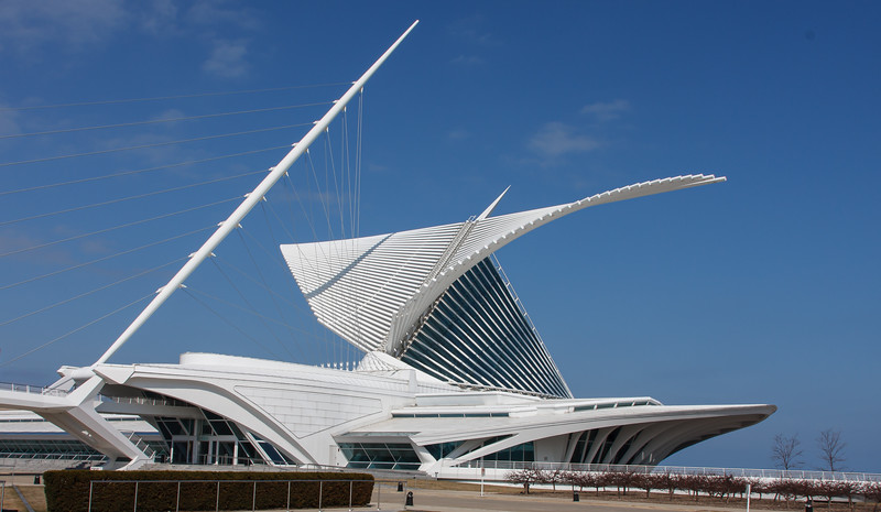 """The Quadracci Pavilion is the iconic sculptural addition to the Milwaukee Art Museum designed by Santiago Calatrava. The Spanish architect was inspired by the """"dramatic, original building by Eero Saarinen...the topography of the city"""" and Frank Lloyd Wright's Prairie-style architecture.  The 142,050-square-foot structure was completed in 2001 and houses a grand reception hall, an auditorium, a large exhibition space, a store, two cafés, and parking. Both cutting-edge technology and old-world craftsmanship went into creating the graceful building, which was made largely by pouring concrete into one-of-a-kind wooden forms.  https://mam.org/info/quadracci.php"""