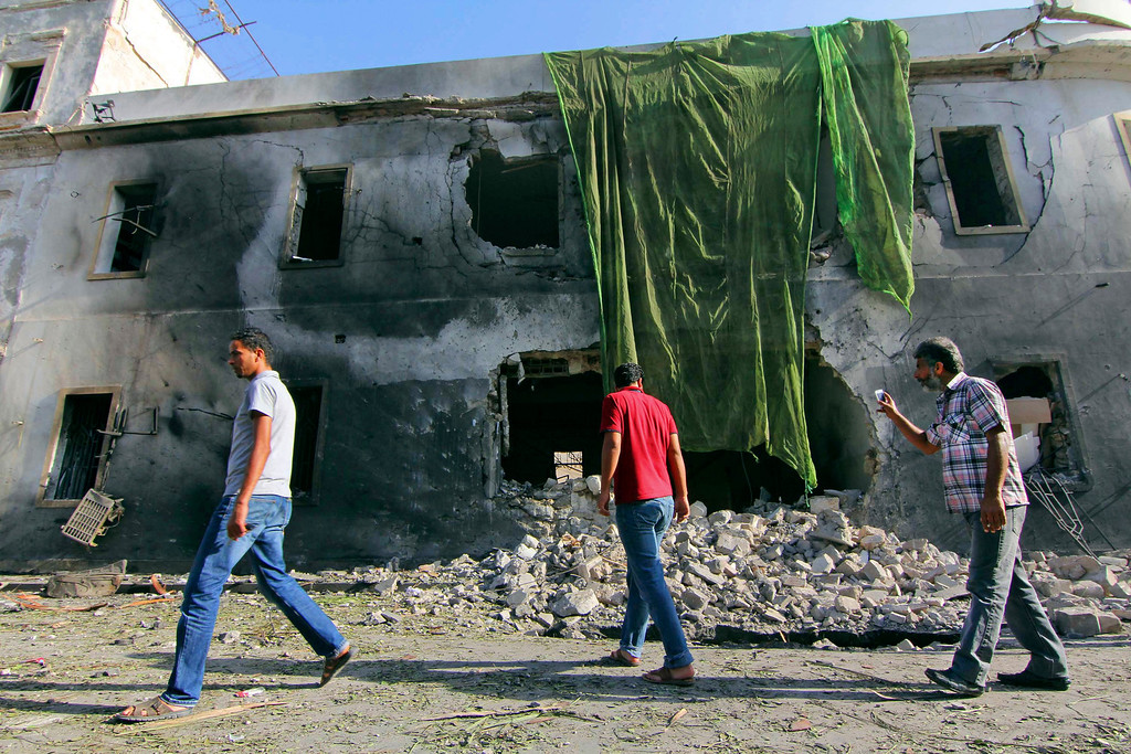 . People gather at the site of a car bombing in Benghazi, Libya, Wednesday, Sept. 11, 2013. A powerful car bomb exploded Wednesday near Libya\'s Foreign Ministry building in the heart of the eastern coastal city of Benghazi, security officials said, one year to the date after an attack there killed the U.S. ambassador and three other Americans. The early morning blast targeted a building that once housed the U.S. Consulate under the rule of King Idris, who former Libyan dictator Moammar Gadhafi overthrew in a 1969 bloodless coup. (AP Photo/Mohammed el-Shaiky)