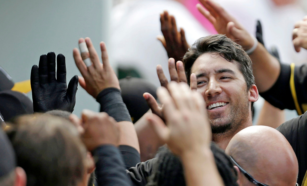 . Pirates first baseman Travis Ishikawa is greeted in the dugout after he took Twins pitcher Vance Worley deep for a two-run homer in the sixth inning. (AP Photo/Gerald Herbert)