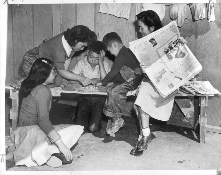 """""""Shade of irony touches this scene, for the young Japanese in the center are playing Chinese checkers.  The mother passes her time with a newspaper, sits nearby to hush any childish arguments which may arise.""""--caption on photograph"""