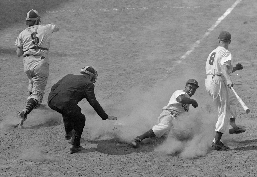 Description of . Jackie Robinson, Dodgers\' second baseman, crosses home plate on a steal from third as Giants\' catcher Walker Cooper (5) fires the ball to third base in the 7th inning of the Brooklyn - New York game at Ebbets Field, New York, July 4, 1948.  Dodgers won 13-12.  At right, is George Shuba, Dodger outfielder who was at bat.  Umpire is Scotty Robb. (AP Photo/Ray Howard)