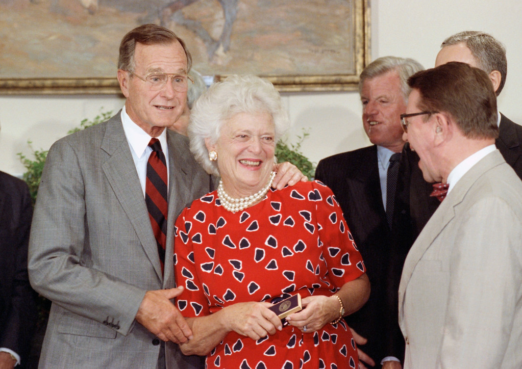 . First Lady Barbara Bush laughs after receiving the pen President Bush used to sign the National Literacy Act of 1991 during a ceremony at the White House in Washington, Thursday, July 26, 1991. Sen. Paul Simon, D-Ill, right, suggested that the pen, which is traditionally given as a souvenir to the chief sponsors of a bill, be given to Mrs. Bush. Sen. Edward Kennedy, D-Mass., is third from left. (AP Photo/Marcy Nighswander)