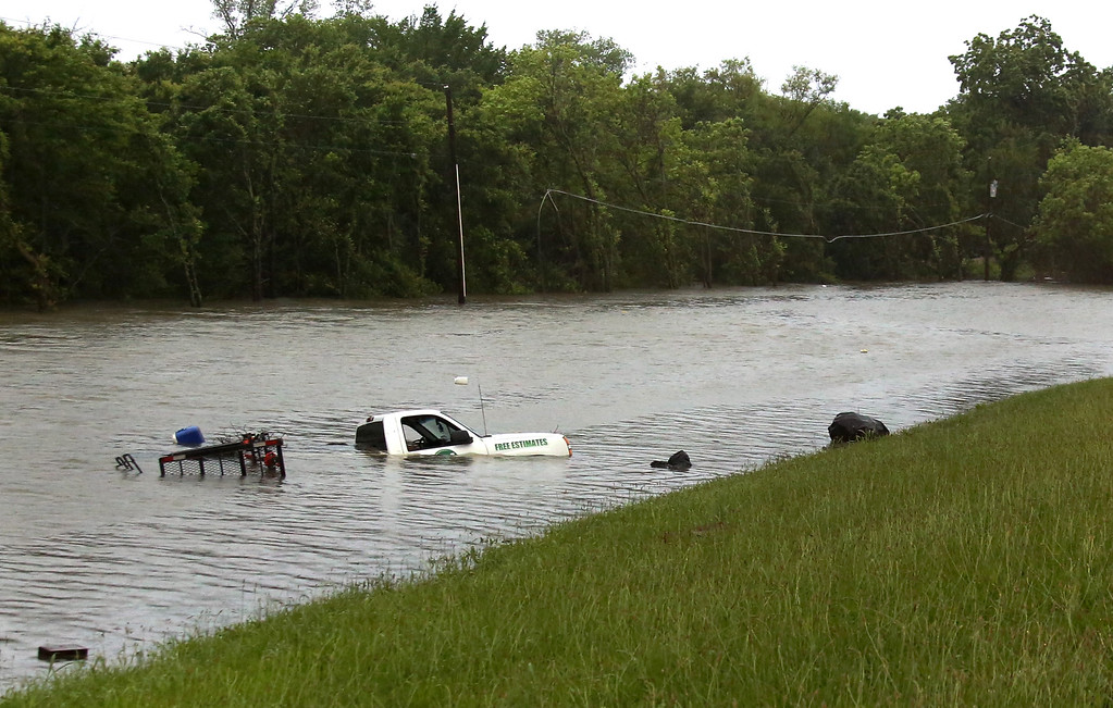 . A truck rests near CF Hawn Freeway, Monday, May 25, 2015, in Dallas. The occupants escaped without harm after the truck was swamped by rising flood waters. Several people were reported missing in flash flooding from a line of storms that stretched from the Gulf of Mexico to the Great Lakes. (Louis DeLuca/The Dallas Morning News via AP)