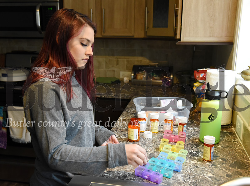Harold Aughton/Butler Eagle: Tara Burk of Boyers prepares her pill containers for the week. Burk who had a double lung transplant 18 months ago has returned to work.