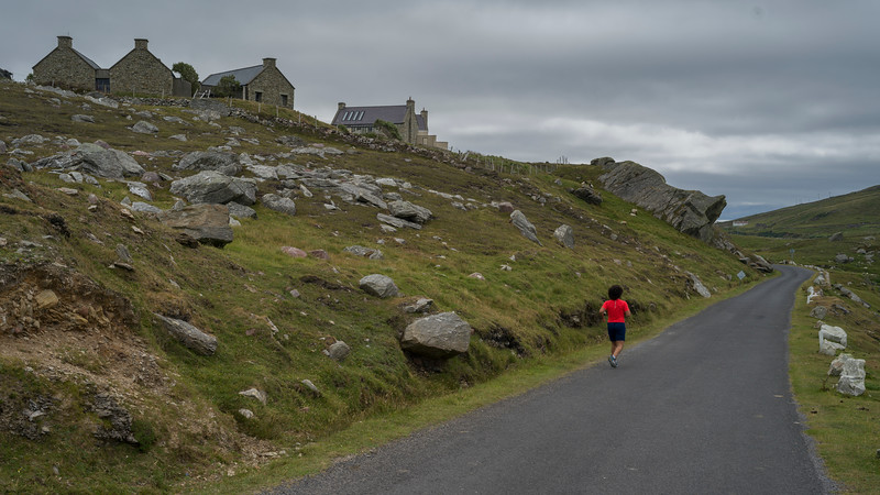 Rear view of woman jogging on the road, Achill Island, County Mayo, Ireland