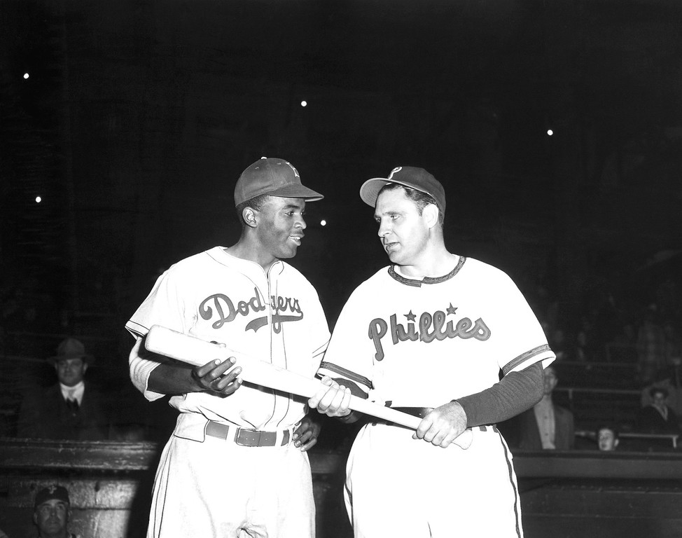 . FILE - In a May 9, 1947 file photo, Jackie Robinson, left, Brooklyn Dodgers\' first baseman, looks over the bat Philadelphia Phillies manager Ben Chapman uses during practice, as he prepared to play his first Philadelphia game for the Dodgers. The Philadelphia City Council unanimously passed a resolution Thursday, March 31, 2016, naming April 15, 2016 as a day to honor Robinson\'s achievements and to apologize for the racism he faced while visiting Philadelphia in 1947. Robinson was refused service by a local hotel and then taunted by Philadelphia Phillies manager Ben Chapman, who, along with players, mercilessly hurled racial slurs at Robinson each time he came to bat. (AP Photo, File)