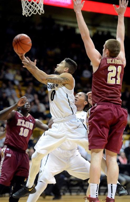 . Askia Booker of CU slips under Ryley Beaumont of Elon during the first half of the December 13, 2013 game in Boulder. (Cliff Grassmick/Boulder Daily Camera)