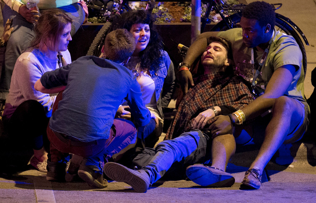 . Unidentified people are comforted after being struck by a vehicle on Red River Street in downtown Austin, Texas, during SXSW on Wednesday March 12, 2014.   (AP Photo/Austin American-Statesman, Jay Janner)
