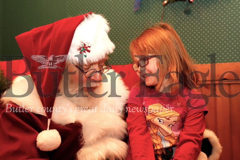 Elena Martini, 5, of Zelienople tells Santa what she wants for Christmas Thursday at the towns Miracle on Main Street festival. Seb Foltz/Butler Eagle