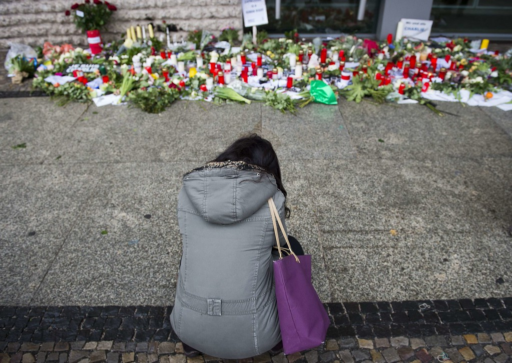 . A woman reacts as flowers and candles are placed in front of the French embassy in Berlin on January 8, 2015, in commemoration of the victims of an attack by armed gunmen on the offices of French satirical newspaper Charlie Hebdo in Paris on January 7 which left at least 12 dead and many others injured. AFP PHOTO / ODD  ANDERSEN/AFP/Getty Images